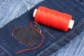 Heart-shaped patch on jeans wiht needle and thread closeup — Stock Photo
