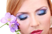 Beautiful female eyes with bright blue make-up and flower — Stock Photo