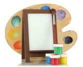 Photo frame as easel with artist's tools isolated on white — Foto Stock