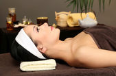 Beautiful young woman in spa salon, on dark background — Stock Photo