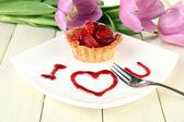 Gâteau sucré aux fraises sauce sur plaque, sur fond de bois — Photo