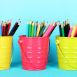 Colorful pencils in three pails on blue background — Stok fotoğraf