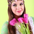 Young beautiful girl with decorative wreath on her head holding bouquet of flowers, on green background - Stock Photo