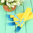 Blue plastic forks wrapped in yellow paper napkins, on color wooden background - Stock Photo