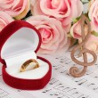 Treble clef, roses and box holding wedding ring on musical background — Stock Photo