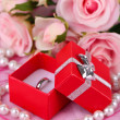 Rose and engagement ring on pink cloth - Stock Photo