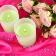 Candle on pink fabric close -up - Foto Stock