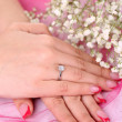 Hands and ring and flowers on a pink background — Stock Photo