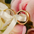 Wedding rings tied with ribbon on rose background - Stock Photo