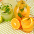 Orange and lemon lemonade in pitchers and glasses on wooden table close-up — Stok fotoğraf