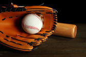 Baseball glove, bat and ball on dark background — Stock Photo