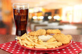 Fried chicken nuggets with french fries,cola and sauce on table in cafe — Stock Photo