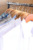 Men's shirts on hangers in wardrobe — ストック写真