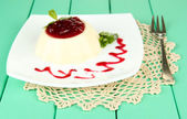 Panna Cotta with raspberry sauce, on color wooden background — Stock Photo
