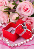 Rose and engagement ring on pink cloth — Stock Photo