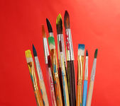 Many brush in paint on red background — Stok fotoğraf