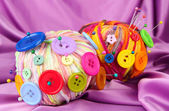 Colorful buttons and multicolor wool balls, on color fabric background — Foto Stock