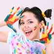 Stock Photo: Young pretty painter with hands in paint, on gray background