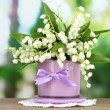 Beautiful lily of the valley in vase on nature background - Stock Photo