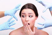 Rubber gloves touching face of young woman close up — Stock Photo