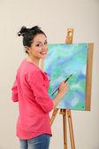 美丽的年轻女子画家在彩色背景上的工作, — 图库照片
