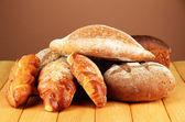 Composição com pão e pãezinhos na mesa de madeira, na cor de fundo — Fotografia Stock