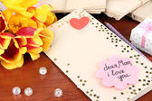 Writing letter of congratulations to mother's Day on wooden table close-up — Stok fotoğraf