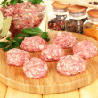 Raw meatballs with spices on wooden table — Stock Photo #24937801