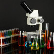 Test tubes with colorful liquids and microscope on dark grey background — Stock Photo
