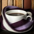 Cup of coffee wrapped in scarf on books background — Foto Stock #24938299