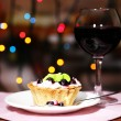 Tasty blackberry cake and glass of red wine, on dark background with bokeh  defocused lights — Stock Photo