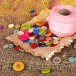 Beautiful buttons and a ball of yarn on a bright background — Stock Photo