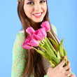 Young beautiful girl with decorative wreath on her head holding bouquet of flowers, on blue background — Stock Photo