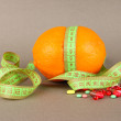 Stock Photo: Orange with measuring tape and multicolor pills, on color background