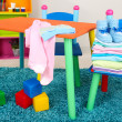 Small and colorful table and chairs with baby clothes — Stockfoto