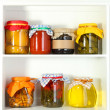 Homemade preserves on beautiful white shelves — Stock Photo #24939309