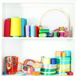 Beautiful white shelves with thread and material for handicrafts — Stock Photo #24939319