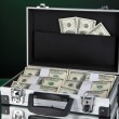 Suitcase with 100 dollar bills isolated on black — Stock Photo #24939575