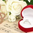 Treble clef, roses and box holding wedding ring on musical background — Stock Photo #24939769