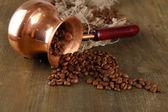 Cafetera con café en grano sobre fondo de madera — Foto de Stock