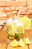 Glass of cocktail with lime and mint on wooden table on bright background — Stock Photo
