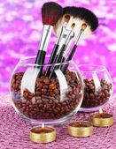 Cuencos de vidrio con granos de café, pinceles y velas sobre fondo brillante — Foto de Stock