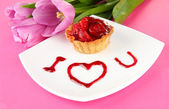 Sweet cake with strawberry and sauce on plate, on color background — Stock Photo