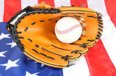 Baseball-handschuh und ball auf amerikanischen flagge hintergrund — Stockfoto