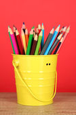 Colorful pencils in pail on table on red background — Stock Photo
