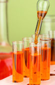 Pipetta di laboratorio con una goccia di liquido di colore sopra le provette di vetro, da vicino — Foto Stock