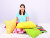 Hermosa joven con almohadas en habitación — Foto de Stock
