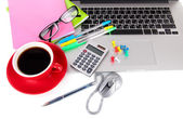 Laptop with stationery and cup of coffee isolated on white — Stock Photo