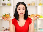 Chica bonita selecciona pizza o dieta sobre fondo de cocina — Foto de Stock