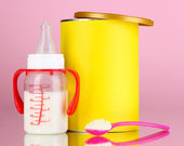 Bottle with milk and food for babies on pink background — Stock Photo